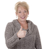 Woman showing thumbs up. Casual blond woman in her fifties on white isolated background Stock Photo
