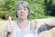 Woman showing thumbs up and down Stock Photo