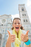 Woman showing thumbs up in front of duomo, italy Stock Photo