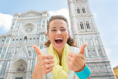 Woman showing thumbs up in front of duomo, italy. Happy young woman showing thumbs up in front of duomo in florence, italy royalty free stock image