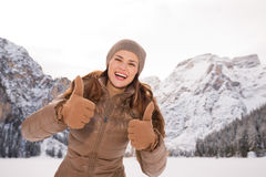 Woman showing thumbs up outdoors among snow-capped mountains Royalty Free Stock Images