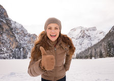 Woman showing thumbs up outdoors among snow-capped mountains Stock Photography