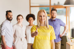 Woman showing thumbs up over creative office team Royalty Free Stock Photography