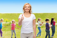 Woman showing thumbs up over group of little kids Royalty Free Stock Images