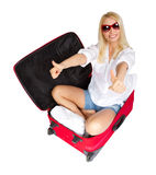 Woman showing thumbs up in travel suitcase. Woman showing thumbs up, sitting in travel red suitcase. Packed for vacation in summer resort. Isolated over white Royalty Free Stock Photo