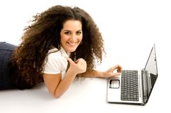 Woman showing thumbs up and working on laptop Stock Images