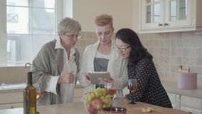 Woman showing to her friends photos on tablet. Group of three mature women communicating chatting spending time in