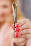 Woman showing tweezers for eyebrows depilating Stock Image