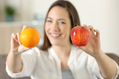 Woman showing two different fruits. Front view portrait of a happy woman showing two different fruits sitting on a couch in the living room at home stock image
