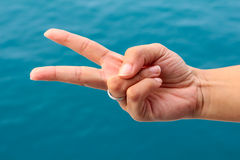 Woman showing two fingers  on sea samui background Royalty Free Stock Photography