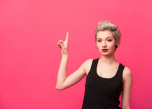 Woman showing up with her finger on pink background. Stock Photos