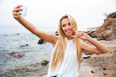 Woman showing v gesture and making selfie on the beach. Young smiling beautiful woman showing v gesture and making selfie while standing on the rocky beach Royalty Free Stock Photo