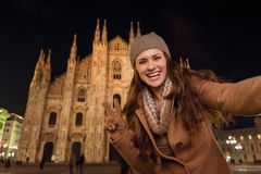 Woman showing victory gesture and taking selfie near Duomo Royalty Free Stock Image