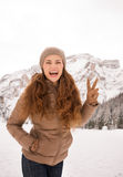 Woman showing victory outdoors among snow-capped mountains Stock Photography
