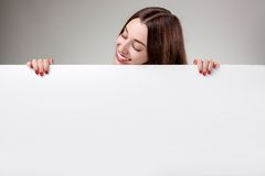 Woman showing white billboard over grey background Stock Photo