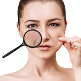 Woman shows age-related mimic wrincles. Woman with magnifying glass shows age-related mimic wrincles on her face stock image