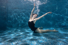 Woman shows beautiful poses underwater. Stock Photo