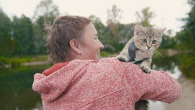 Woman shows the British Shorthair Tabby cat near forest river, outdoor Royalty Free Stock Images