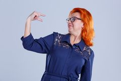 A woman shows a gesture of some sort of measure and looks at it against a gray background. A woman, aged with red hair, in a blue dress, shows a gesture of some royalty free stock photos