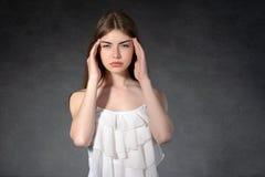 Woman shows that she had a headache Stock Photos
