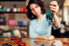 Woman shows handmade bracelet, needlework hobby. Female master at the workplace, craftmans tools on the table Royalty Free Stock Image