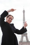 Woman shows with hands how high Eiffel Tower Royalty Free Stock Photography
