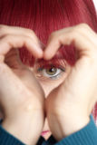Woman shows heart. Detail of a formed hand with heart and eye Stock Image