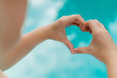 Woman shows heart by hands. Pool on background Stock Photography