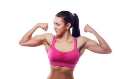 Woman shows her bicep. A woman in pink sports clothes shows her bicep. Isolated white background Stock Photos