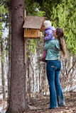 Woman shows her daughter the bird feeder Royalty Free Stock Photography