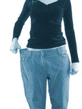 Woman shows her weight loss by wearing an old big trousers. Royalty Free Stock Photography