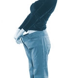 Woman shows her weight loss by wearing an old big trousers. Royalty Free Stock Photos