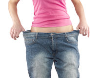 Woman shows her weight loss by wearing an old big trousers. Royalty Free Stock Image