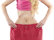 Woman shows her weight loss by wearing an old big trousers. Royalty Free Stock Images