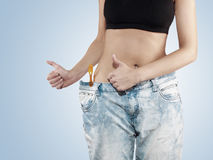Woman shows her weight loss by wearing an old jeans. Stock Image