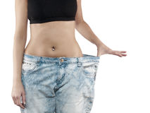 Woman shows her weight loss by wearing an old jeans. Royalty Free Stock Photography
