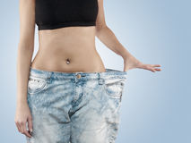 Woman shows her weight loss by wearing an old jeans. Stock Photography