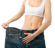 Woman shows her weight loss by wearing an old jeans, isolated on Royalty Free Stock Photos