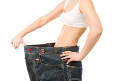 Woman shows her weight loss by wearing an old jeans. isolated on Royalty Free Stock Photos