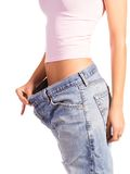 Woman shows her weight loss by wearing an old jeans, isolated on white background Royalty Free Stock Photo