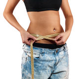 Woman shows her weight loss by wearing an old jeans. Stock Images