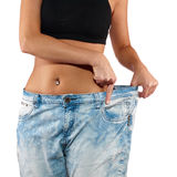 Woman shows her weight loss by wearing an old jeans. Royalty Free Stock Image