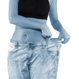 Woman shows her weight loss by wearing an old jeans. Royalty Free Stock Photos