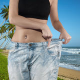 Woman shows her weight loss by wearing an old jeans. Stock Photo