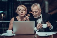 Woman shows on Laptop and Man drink coffee royalty free stock photography