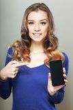 Woman shows a look at a smartphone Stock Image