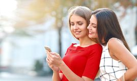 Woman shows on a mobile phone something to his girlfriend royalty free stock images