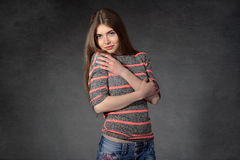 Woman shows the modesty against a dark background Stock Photo