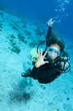 Woman shows off her wedding ring on a dive. Female scuba diver shows off her wedding ring Stock Photo