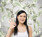 Woman shows ok sign. Dollar notes are falling down over concrete background. Stock Photography